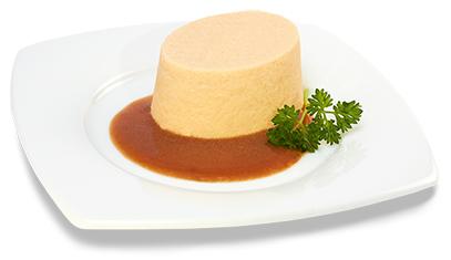 Passierte Schweinefleisch-Timbale, auf einem Teller angerichtet
