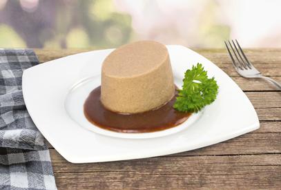 Passierte Fleisch-Timbale, auf einem Teller angerichtet